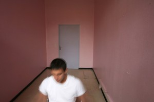 Homme seul dans une piece rose.
