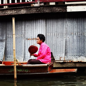 Vendeuse assise dans son bateau pendant le marche flottant. Thailande.